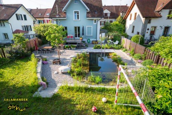 Quartiergarten mit Schwimmteich Natursteinmauern Kiesplatz und Rasenfläche