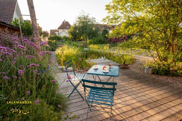 gemütlicher Sitzplatz im Bilderbuch-Naturgarten mit Schwimmteich und Holzdeck
